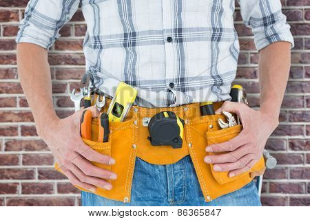 Cropped image of technician with tool belt around waist against red brick wall