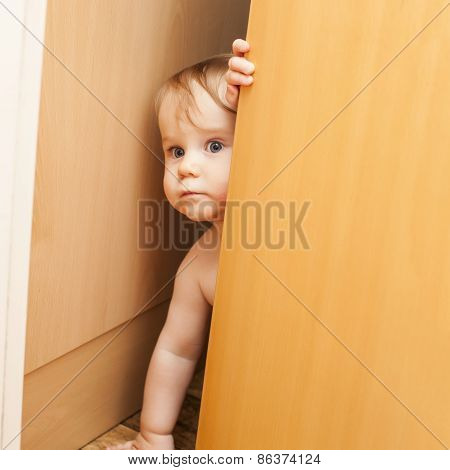 Curious Cute Baby Boy Looking Through Ajar Door