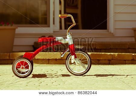 Child's rusted favorite cherished red tricycle standing ready and waiting for its owner to arrive on paving outside a house poster