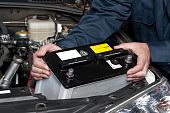 A car mechanic replaces a battery in a car. poster