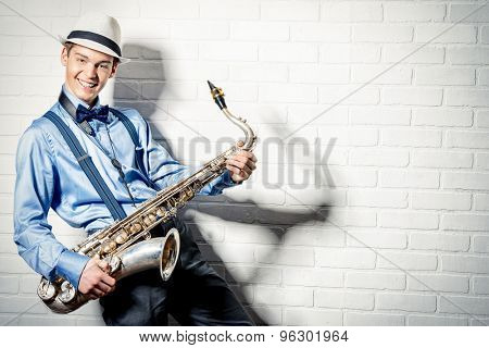 Young expressive musician playing the saxophone. Art and music. Jazz music.