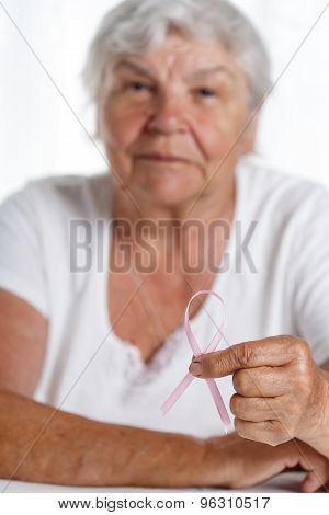 Elder Woman Holding Pink Breast Cancer Awareness Ribbon In Hand