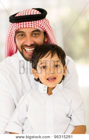 portrait of arabian father and son sitting at home