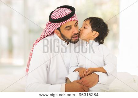 cute little muslim boy kissing his father indoors