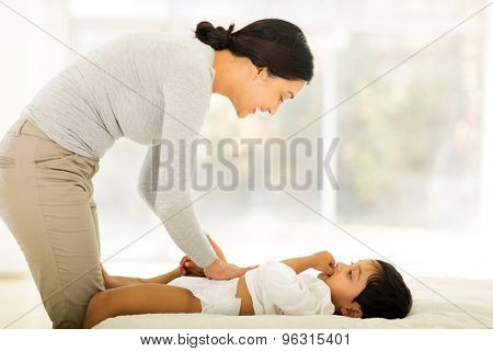 happy indian mother changing baby nappy