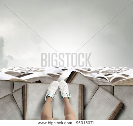 Close up of woman legs standing on the edge of rock of books