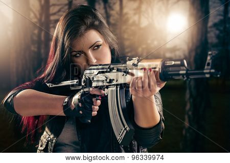 Attractive girl in forest standing in the attitude of aiming and looking through the sight automatic rifle. poster