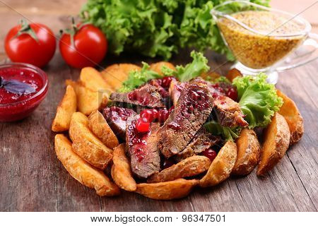 Beef with cranberry sauce, roasted potato slices and bun on wooden cutting board, close-up
