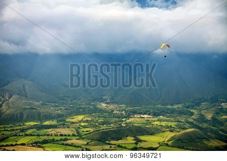 Paragliding In Mountains Above Fields And Villages - View From Air