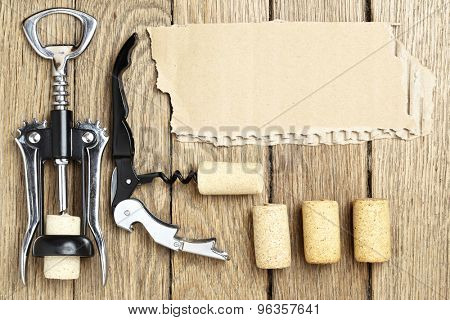 Still life with two cork-screws, wine corks and cardboard for text