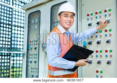 Asian Indonesian Technician or electrician making function test on Panel or switchbox for the control of air conditioners on construction site or in factory for acceptance