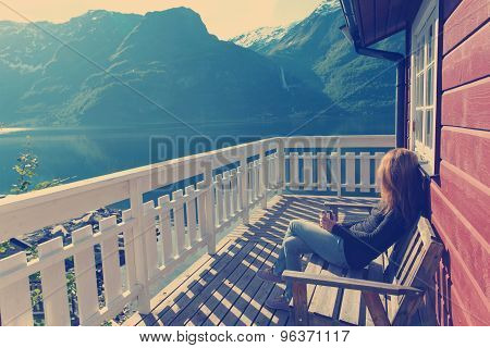 girl sitting near rorbu and admires the beautiful Norwegian landscape at the fjord and mountains poster