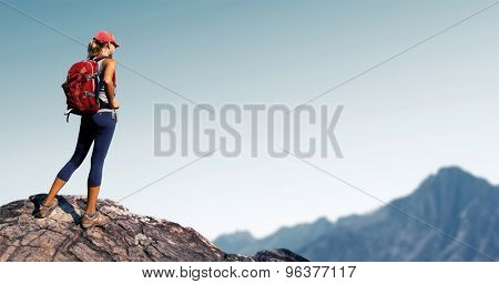 Lady hiker standing on top of the hill with clear sky and mountains on the background