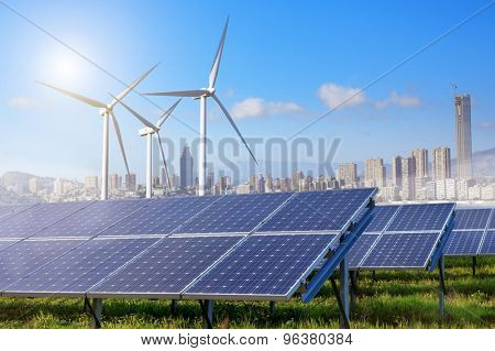 solar panels and wind turbines under sky and clouds with city on horizon. Sunrise