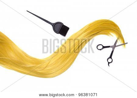 Long golden blonde hair with professional scissors and hair dye brush, isolated on white background