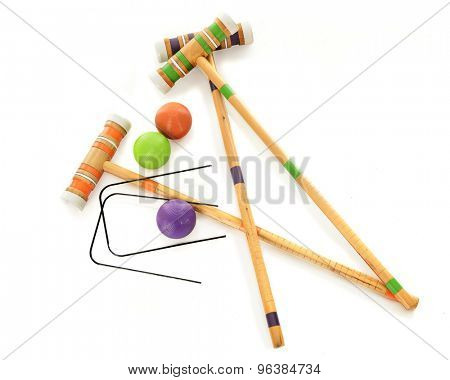 Overhead view of three wooden croquet mallets with matching balls and two black wickets.  On a white background.
