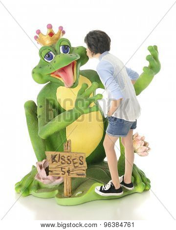 A young teen girl kissing a delighted frog prince.  The price ...only five cents!  On a white background.