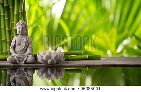 Buddha in meditation with burning candle