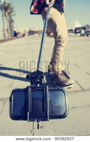 a young skater on his skateboard takes a self-portrait or a video of himself with a selfie stick