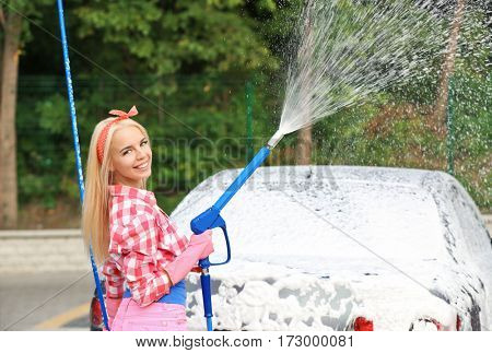 Woman washing car with high pressure foam