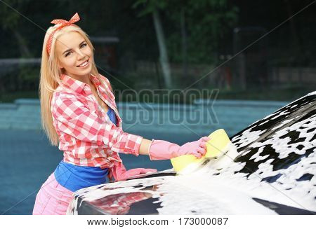 Woman washing car with sponge