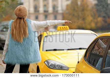 Woman catching yellow taxi on the street