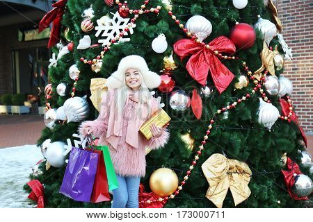Woman with gift box and shopping bags on Christmas tree background
