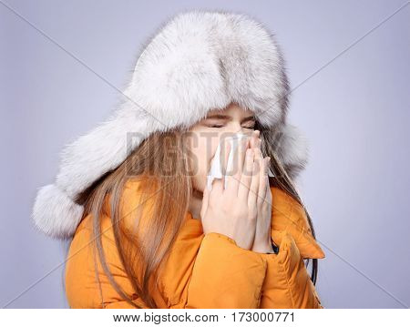 Young ill woman with tissue on color background