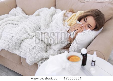 Young ill woman lying in bed at home