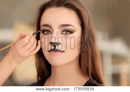 Visagiste applying cat makeup onto face of beautiful young woman in salon