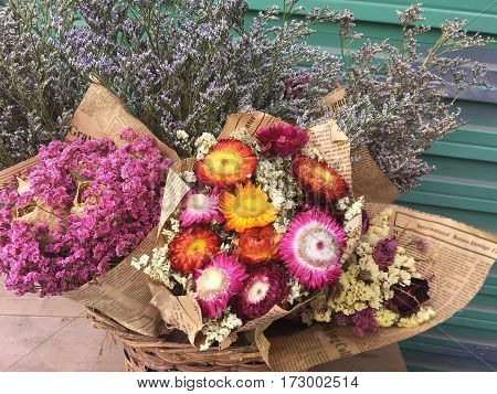 Closeup of beautiful dry flowers vintage background. Bouquet of dried flowers wrapped in old newspaper on wooden background.