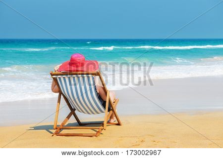 Happy woman in red sunhat on the beach sitting on deckchair and looking into the sea.Vacation and travel concept.