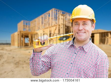 Smiling Male Contractor in Hardhat Holding Blueprints  and Level at Home Construction Site.