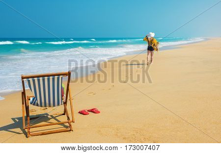 Deckchair and woman in white sunhat going along the beach .Vacation and travel concept.