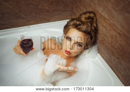 Young cute girl drinking red wine in bath with foam. She relaxes after a hard day. Girl coquettishly looks up and sends an air kiss.