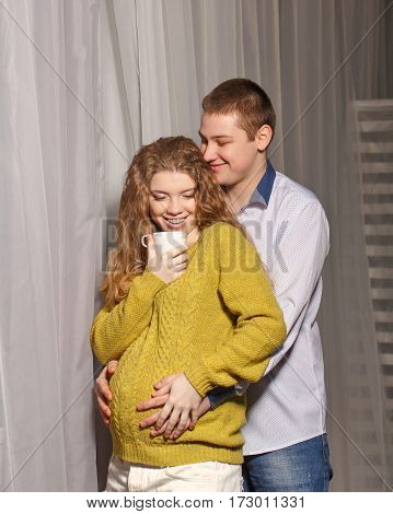 Husband embracing his pregnant wife. Lovely girl in sweater drinking a hot drink from a cup. Happiness and understanding in the family. They are smiling