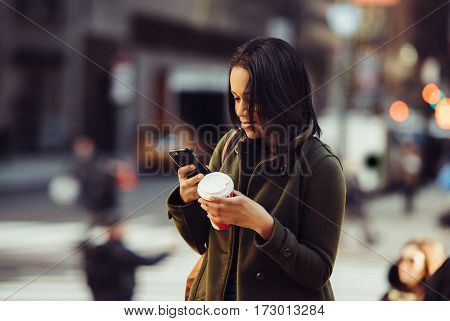 Young adult energetic woman texting on cell phone drinking coffee and walking to work on city street