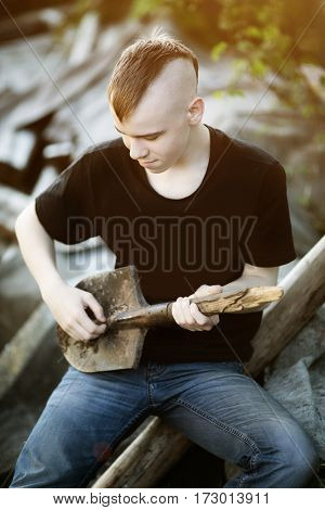 Teen boy with a shovel as a guitar in his hands. Difficult awkward age. Problem teenager in with Mohawk hairstyle