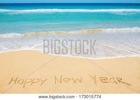 Happy New Year message on the beach sand - new year vacation and travel concept