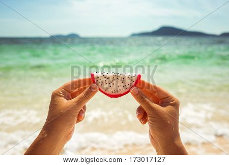 beautiful girl holding hands Pitaya fruit on a background of blue sky and sea. dragon fruit. Good mood.