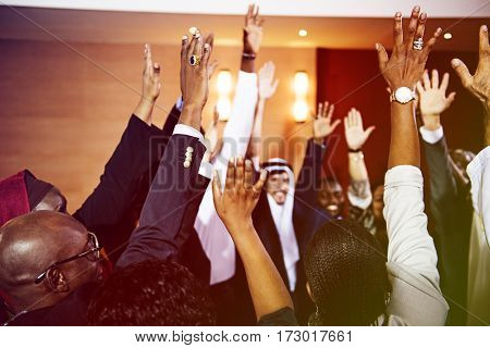 Diverse group of people with hands raised united
