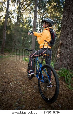 Female biker with mountain bike in countryside forest