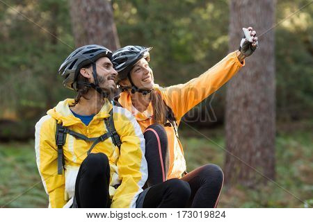 Biker couple taking selfie from mobile phone at countryside forest