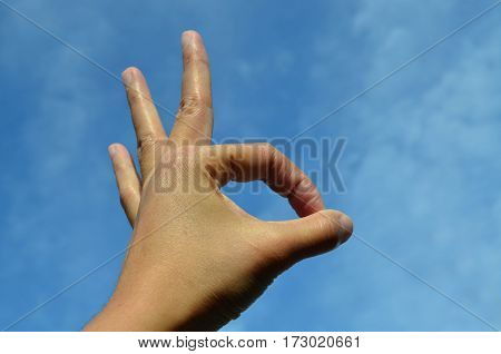 Asian woman hand showing ok gesture or peace against blue sky background