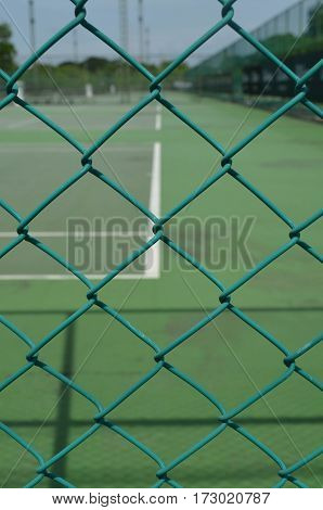 Green security wire mesh fence with blurred tennis court background