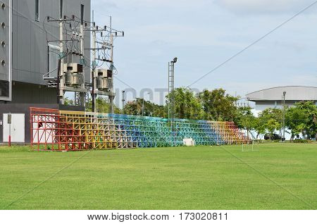 Empty colorful metal grandstand at green football field