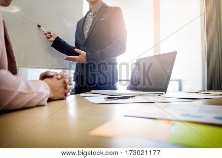 Businesswoman Asking Question During Her Colleagues Presentation In Bright Office
