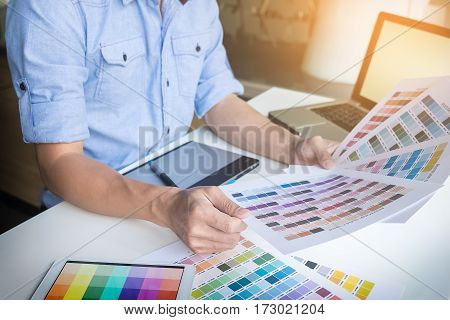 young graphic designer working on a desktop computer and using some color swatches top view.