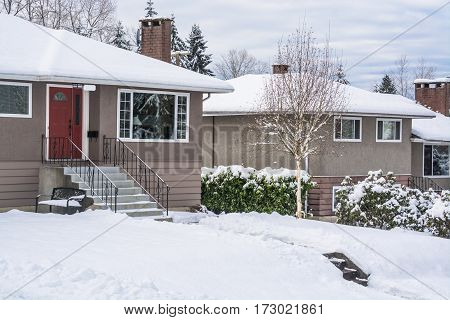 Street of family houses and front yards in snow. North American houses on winter cloudy day