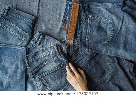Choosing Jeans, Top View Of Hand And Jeans On Blue Fabric Background